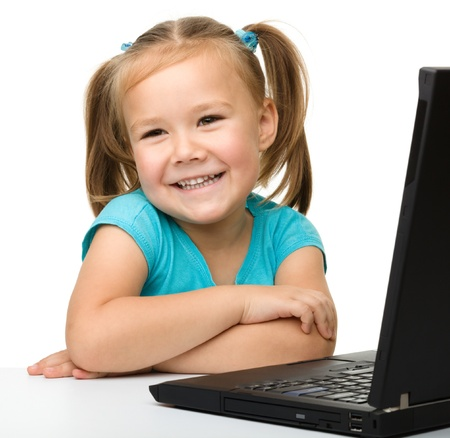 Cute little girl is sitting at table with her black laptop, isolated over white photo