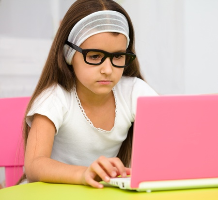 Cute little girl is sitting at table with her pink laptop and wearing glasses photo