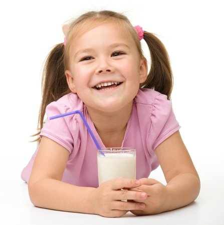 Cute little girl with a glass of milk, isolated over white photo