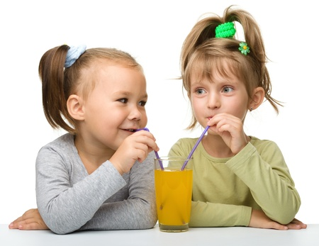 Two Little girls are drinking orange juice from one glass using straw, isolated over white photo