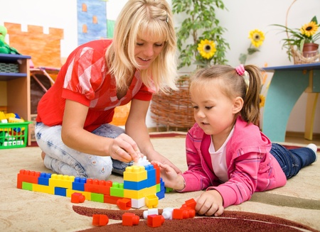 kindergarten teacher: Teacher and child are playing with building bricks in preschool Stock Photo