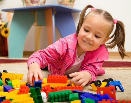 Little girl is playing with building bricks in preschool while laying on floor photo