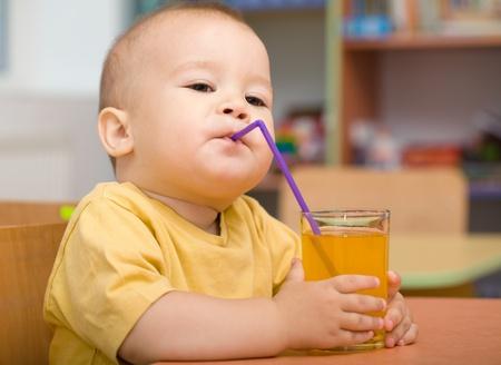 tomando jugo: Lindo niño está bebiendo el jugo de naranja a partir de paja
