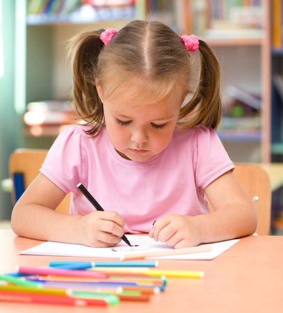 Cute little girl is drawing with felt-tip pen in preschool Stock Photo - 11872384