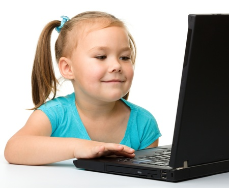 Cute little girl is sitting at table with her black laptop, isolated over white Stock Photo - 11872538