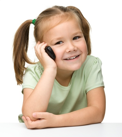 Cute little girl is talking on cell phone while sitting at table, isolated over white photo