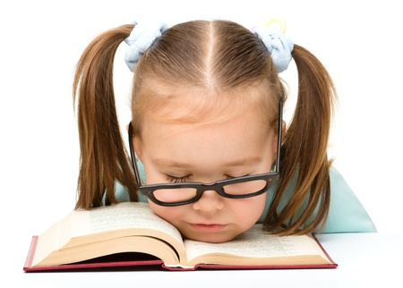 Cute little girl is sleeping on a book while wearing glasses, isolated over white Stock Photo