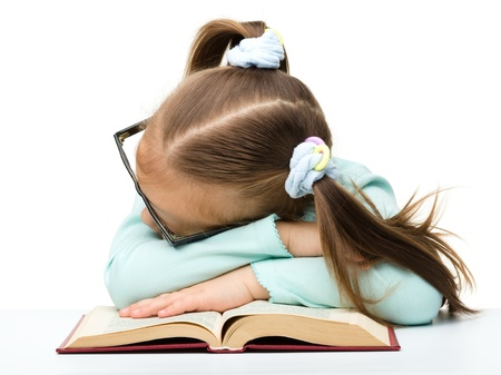 Cute little girl is sleeping on a book while wearing glasses, isolated over white photo