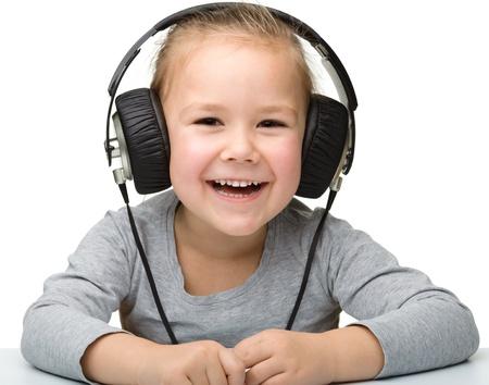 Cute little girl enjoying music using headphones, isolated over white photo
