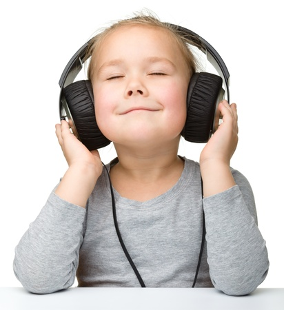 Cute little girl enjoying music using headphones, isolated over white Imagens