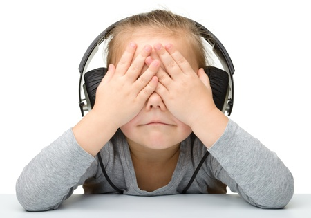 Unhappy girl listening music using headphones while covering her eyes, isolated over white photo