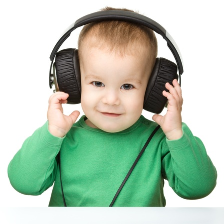 Cute little boy enjoying music using headphones, isolated over white photo