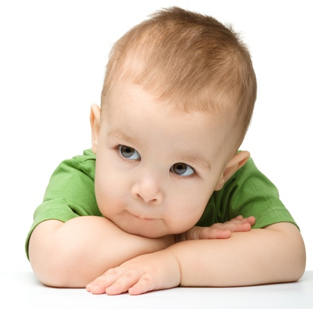 Portrait of a cute and pensive little boy support his head with hands, isolated over white photo