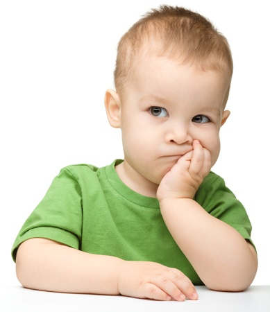 Portrait of a cute and pensive little boy support his head with hand, isolated over white photo