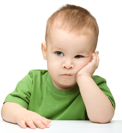mirada triste: Retrato de un niño lindo y pensativo sostener su cabeza con la mano, aislados en blanco