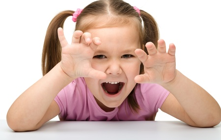 roaring tiger: Cute little girl is showing a scary tiger, isolated over white Stock Photo