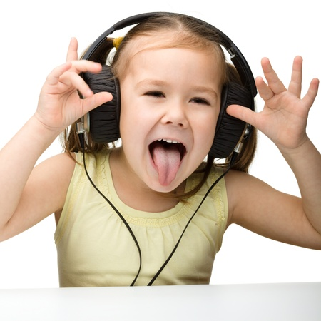 girl tongue: Cute little girl enjoying music using headphones and showing her tongue, isolated over white