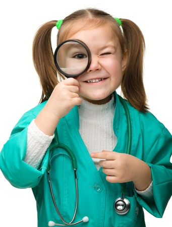 Cute little girl is playing doctor looking through magnifier, isolated over white photo