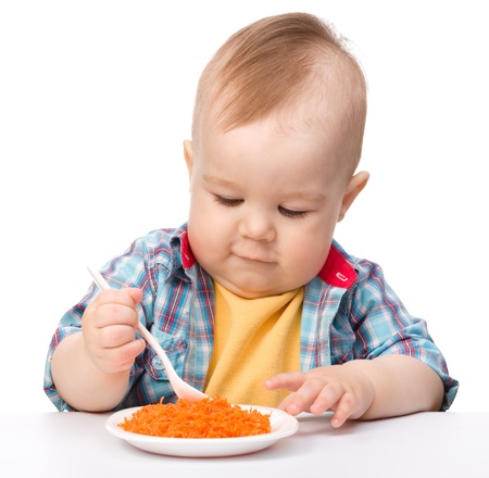 Cute little boy is playing with carrot salad, isolated over white photo