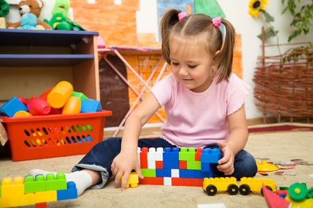 kids learning: Little girl is playing with building bricks in preschool while sitting on floor Stock Photo