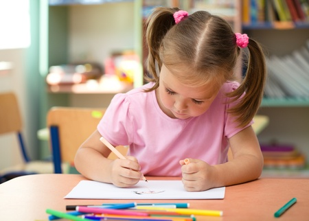 Cute little girl is drawing with felt-tip pen in preschool Imagens
