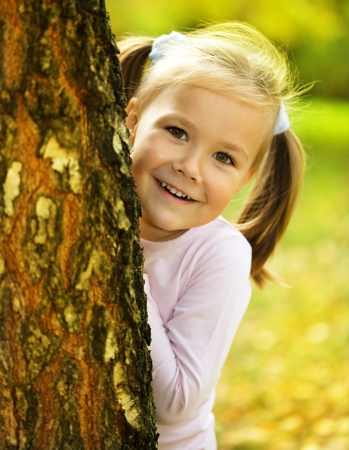 hide and seek: Cute little girl is playing hide and seek outdoors