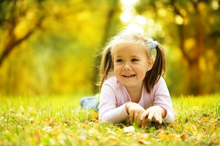 girl in the forest: Cute little girl is playing with leaves in autumn park
