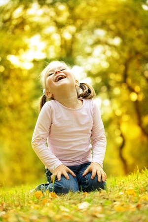 little girl smiling: Cute little girl is playing with leaves in autumn park