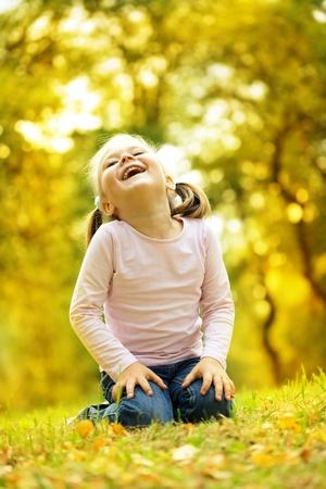 jolie petite fille: Petite fille mignonne joue avec des feuilles en automne parc Banque d'images