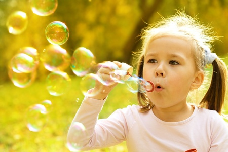 burbujas de jabon: Niña linda está soplando pompas de jabón a
