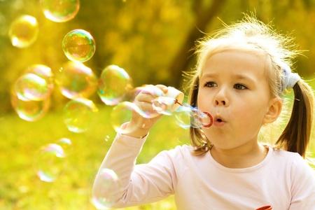 jolie petite fille: Petite fille mignonne est soufflant un des bulles de savon
