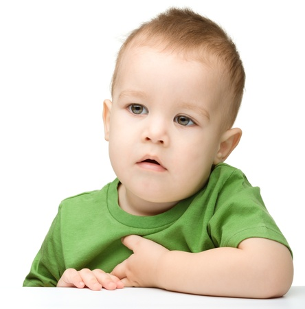 Portrait of a cute and pensive little boy, isolated over white photo