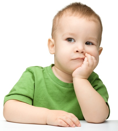 children sad: Portrait of a cute and pensive little boy support his head with hand, isolated over white