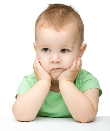 Portrait of a cute and pensive little boy support his head with hand, isolated over white Stock Photo - 12850599