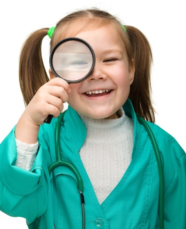 Cute little girl is playing doctor looking through magnifier, isolated over white Stock Photo - 12850684