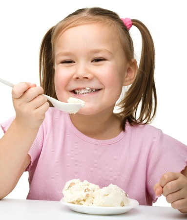 Cute little girl is eating cottage cheese using spoon, isolated over white Imagens