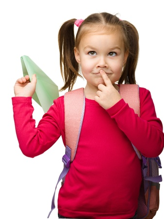 Portrait of little schoolgirl with backpack thinking about something and going to throw a paper airplane, isolated over white photo