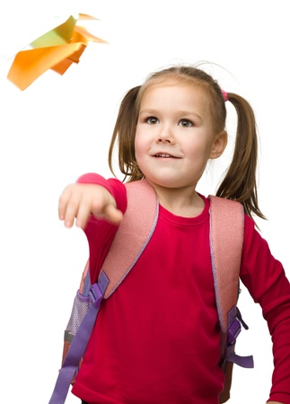 paper airplane: Portrait of little schoolgirl with backpack throwing a paper airplane, isolated over white