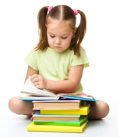 Cute little girl reads a book, isolated over white photo