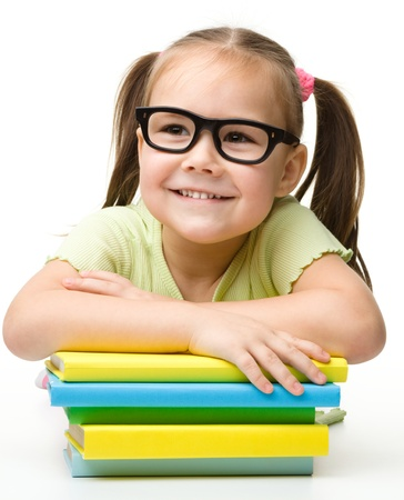 Cute cheerful little girl with books wearing glasses, isolated over white photo
