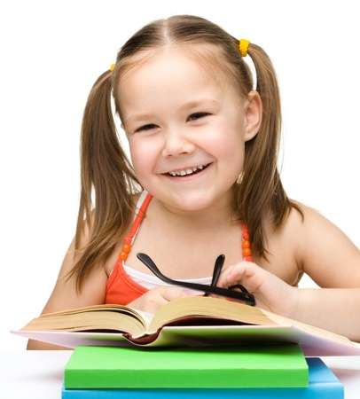 Cute cheerful little girl with books wearing glasses, isolated over white Stock Photo - 13318862