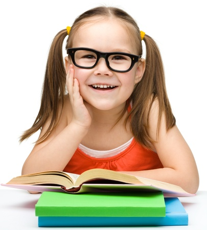 Cute cheerful little girl with books wearing glasses, isolated over white Stock Photo - 13326704