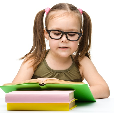 Cute cheerful little girl reading book wearing glasses, isolated over white photo