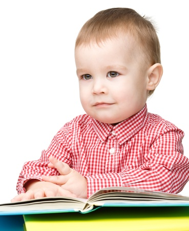Cute little child play with book while sitting at table, isolated over white photo
