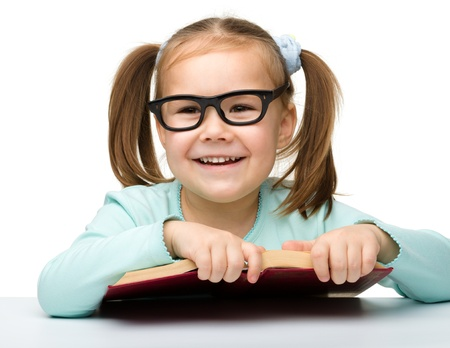 reading glasses: Cute little girl reads a book while wearing glasses, isolated over white