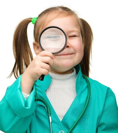 Cute little girl is playing doctor looking through magnifier, isolated over white Stock Photo - 13514207