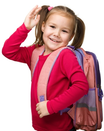 Portrait of a cute little schoolgirl with backpack, going to school and waiving bye-bye, isolated over white photo