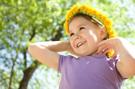 Outdoor portrait of a cute little girl with dandelion wreath photo