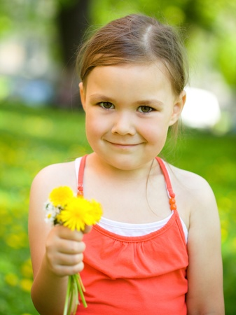 Cute little girl with a bunch of dandelions outdoors photo