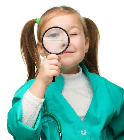 Cute little girl is playing doctor looking through magnifier, isolated over white Stock Photo - 13791391
